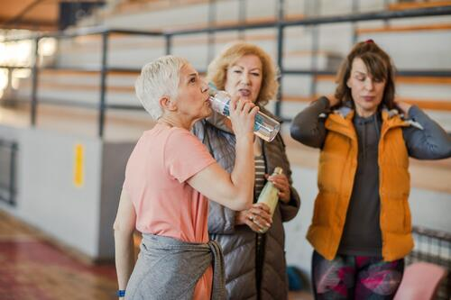 Women drinks from a water bottle after a fitness class with friends