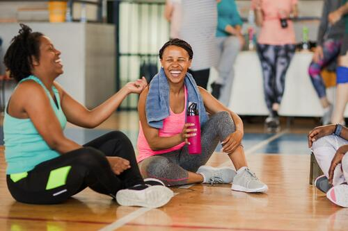 Women talk and laugh after a fitness class